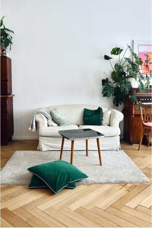 Herringbone natural Scandinavian hardwood, blonde wood flooring, plush pile off-white area rug, green throw pillows, white plush sectional